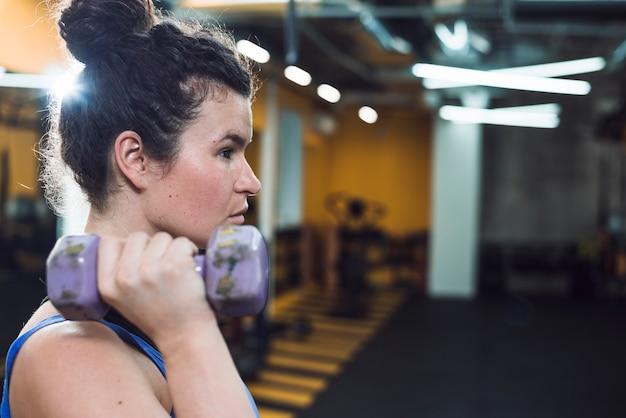 Zijaanzicht van een jonge vrouw die oefening met domoren doet