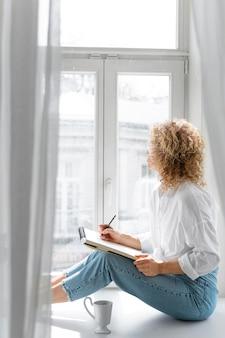 Zijaanzicht van een jonge vrouw die thuis dichtbij het raam tekent