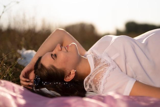 Zijaanzicht van een jonge vrouw die van het weer geniet