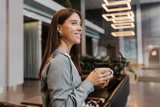 Zijaanzicht van een jonge vrouw die van koffie geniet