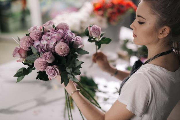Zijaanzicht van een jonge vrouwelijke bloemist die een schort draagt, stelt een nieuw boeket samen van verse bloemen
