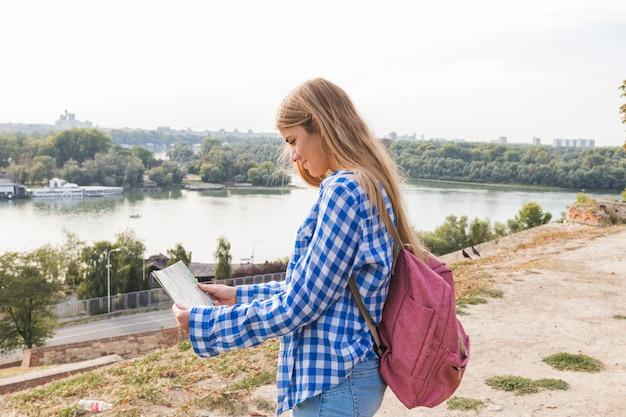 Zijaanzicht van een jonge vrouwelijke wandelaar die richting in kaart zoekt