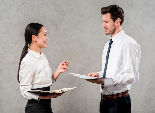 Zijaanzicht van een jonge zakenman en een onderneemster die het project bespreken die zich tegen grijze muur bevinden