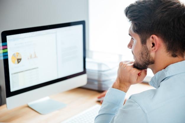 Zijaanzicht van een jonge zelfverzekerde knappe zakenman die op een laptop op kantoor werkt