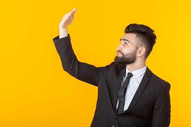 Zijaanzicht van een jonge zelfverzekerde mannelijke zakenman die zijn handpalm bekijkt terwijl hij tegen een gele muur poseert. het concept van zakelijke gadgets en apparaten. plaats voor promo