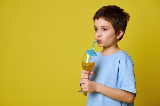Zijaanzicht van een jongen die een heerlijke fruitcocktail drinkt uit een rietje. geïsoleerd op gele muur.