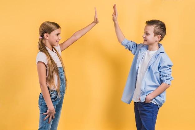 Zijaanzicht van een jongen en een meisje die hoogte vijf geven aan elkaar die zich tegen gele achtergrond bevinden