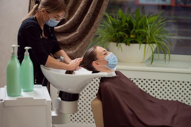 Zijaanzicht van een kapper in zwart uniform en beschermend medisch masker dat het haar van de cliënt in de schoonheidssalon wast