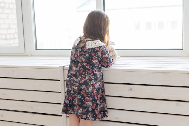 Zijaanzicht van een klein onbekend meisje in een lange bloemenjurk met een favoriet konijntjesstuk speelgoed in haar