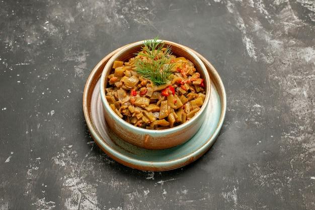 Zijaanzicht van een kom met sperziebonen, sperziebonen met tomaten in een kom op een dienblad op het donkere oppervlak