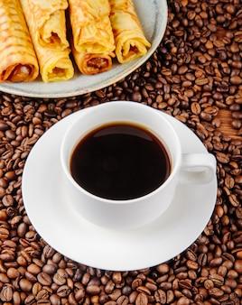 Zijaanzicht van een kop van koffie met wafeltjebroodje dat met condens op een plaat op koffiebonen wordt gevuld