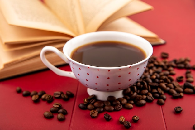 Zijaanzicht van een kopje koffie met koffiebonen geïsoleerd op een rode achtergrond
