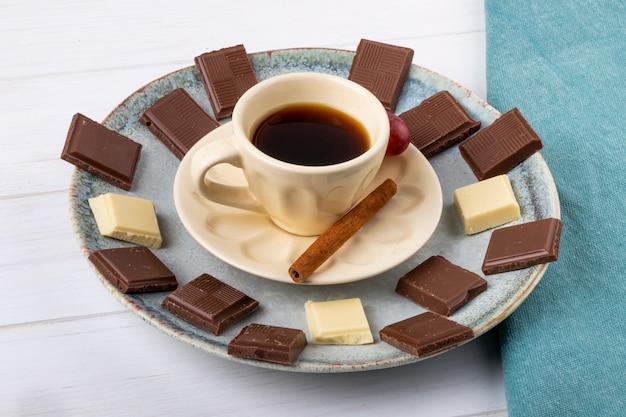 Zijaanzicht van een kopje koffie met witte en donkere chocolade op witte houten achtergrond