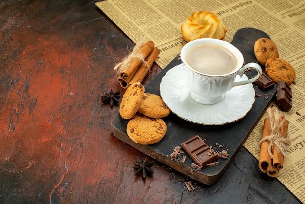 Zijaanzicht van een kopje koffie op een houten snijplank op een oude krant, koekjes, kaneellimoenen, chocoladerepen op donkere achtergrond
