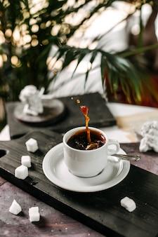 Zijaanzicht van een kopje koffie op een houten snijplank