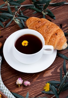 Zijaanzicht van een kopje thee met croissant en paardebloemen op hout