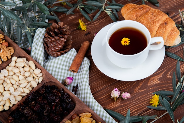 Zijaanzicht van een kopje thee met croissant, gemengde noten met gedroogde vruchten en verspreide paardebloemen op hout