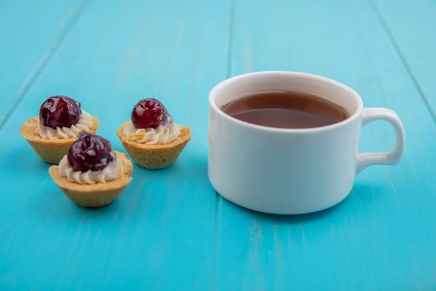 Zijaanzicht van een kopje thee met mini druiventaartjes geïsoleerd op een blauwe houten achtergrond