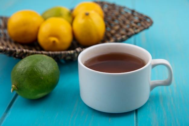 Zijaanzicht van een kopje thee met verse citroenen op een emmer op een blauwe houten achtergrond