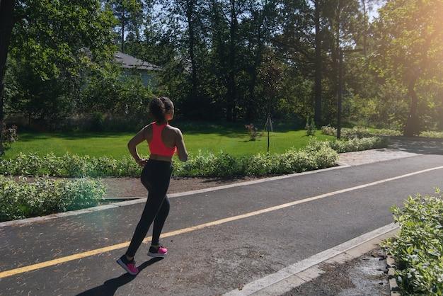 Zijaanzicht van een loper joggen op een lopende manier in het park op de achtergrond van een zonsondergang