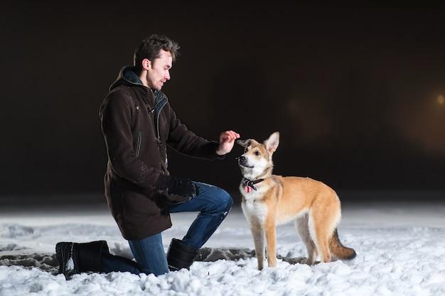 Zijaanzicht van een man die de bastaardhond voedt. beiden zitten 's nachts buiten in de sneeuw in de winter