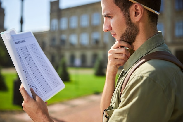Zijaanzicht van een man met een potlood achter zijn oor die een antwoordblad nauwkeurig bekijkt