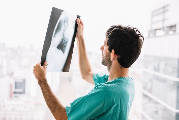 Zijaanzicht van een mannelijke arts die röntgenstraal bekijkt