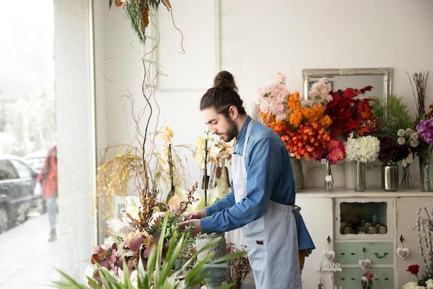 Zijaanzicht van een mannelijke bloemist die de bloemen in zijn bloemwinkel schikt