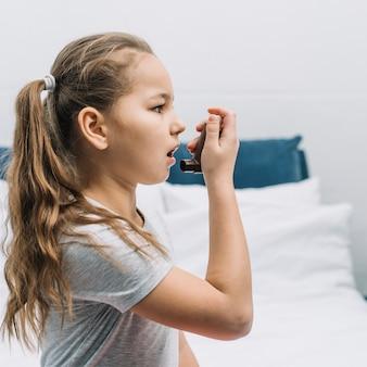 Zijaanzicht van een meisje dat astmainhaleertoestel met behulp van