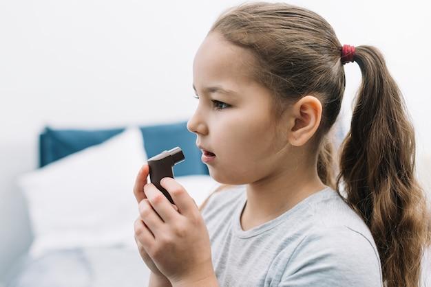 Zijaanzicht van een meisje die astmainhaleertoestel thuis gebruiken