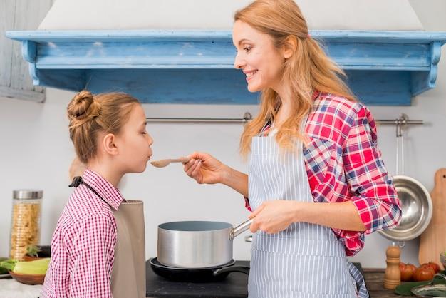 Zijaanzicht van een meisje die het voedsel proeven dat door haar moeder in de keuken wordt voorbereid