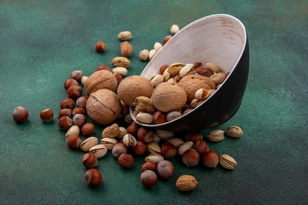 Zijaanzicht van een mix van noten, walnoten, pistachenoten, hazelnoten en pinda's in een kom op een groen oppervlak
