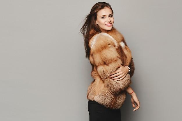 Zijaanzicht van een modelmeisje in een dure luxueuze bontjas die bij de grijze achtergrond wordt geïsoleerd. winter mode.
