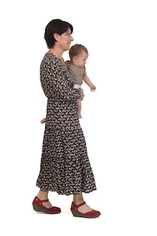Zijaanzicht van een moeder die haar baby draagt lopend op een witte achtergrond