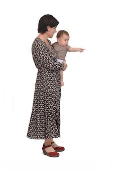 Zijaanzicht van een moeder die haar baby draagt, wijzend op een witte achtergrond