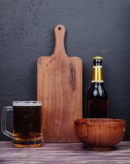 Zijaanzicht van een mok bier met een houten snijplank fles bier en houten kom op zwart