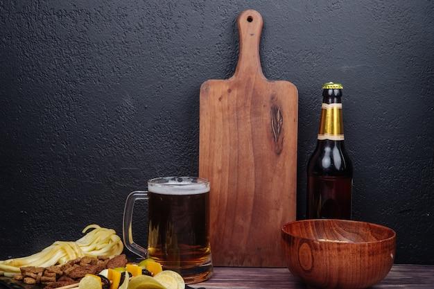 Zijaanzicht van een mok bier met een houten snijplank fles bier en verschillende zoute snacks op zwart