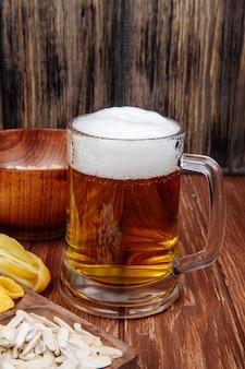 Zijaanzicht van een mok bier met verschillende zoute snacks op rustiek