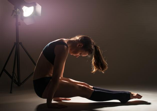 Zijaanzicht van een mooie jonge vrouw atleet in sportkleding doet een handstand poseren in de studio in donkere verlichting