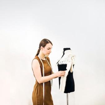 Zijaanzicht van een mooie vrouwelijke ontwerper naaiende kleding