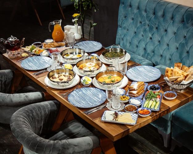 Zijaanzicht van een ontbijttafel met diverse voedsel gebakken eieren geassorteerde ham verse salade en sap