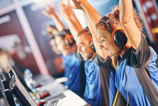 Zijaanzicht van een opgewonden gemengd ras meisje vrouwelijke cybersport gamer die handen opsteekt om te vieren