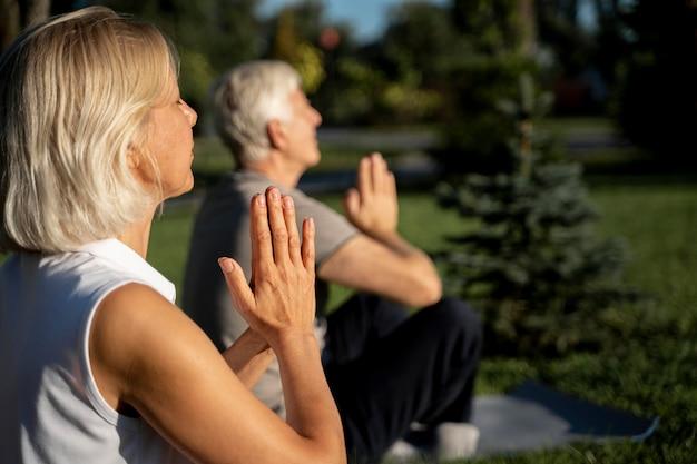 Zijaanzicht van een ouder echtpaar beoefenen van yoga buiten