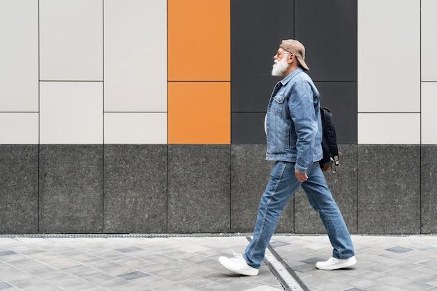Zijaanzicht van een oudere man die buiten in de stad loopt