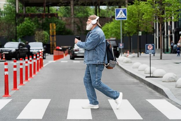 Zijaanzicht van een oudere man die de straat oversteekt terwijl hij naar muziek luistert op een koptelefoon