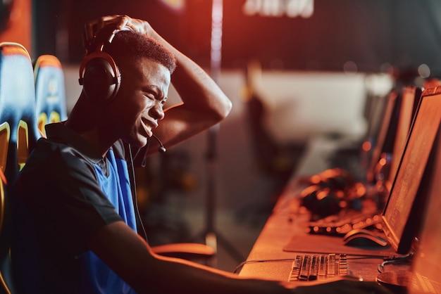 Zijaanzicht van een overstuur afrikaanse mannelijke professionele gamer die een koptelefoon draagt die zich overstuur voelt bij het verliezen van video