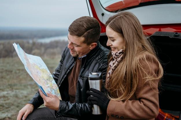 Zijaanzicht van een paar dat een kaart in de kofferbak van de auto controleert