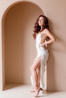 Zijaanzicht van een prachtig lang meisje in een witte jurk poserend op een roze muurachtergrond