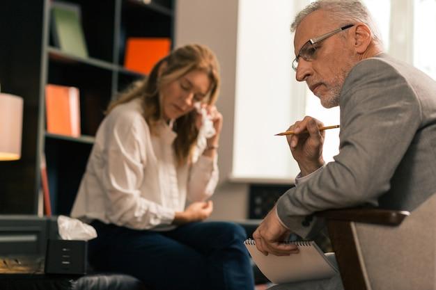 Zijaanzicht van een psychotherapeut die denkt terwijl hij naast zijn huilende vrouwelijke patiënt in zijn kantoor zit