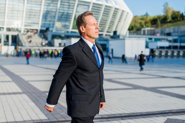 Zijaanzicht van een rijpe zakenman die in bureaucampus loopt